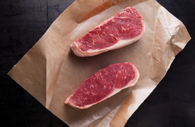 Two cuts of beef on brown paper